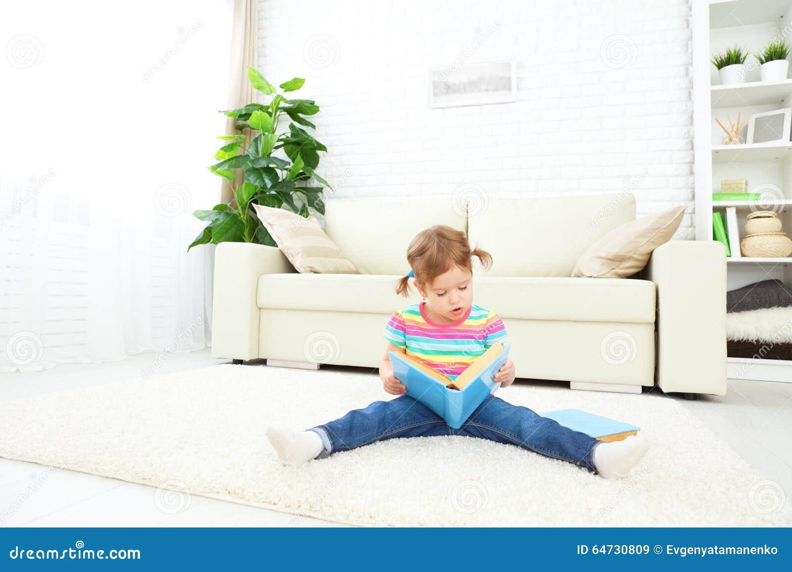 Libro di lettura sveglio della neonata a casa che si siede sul pavimento