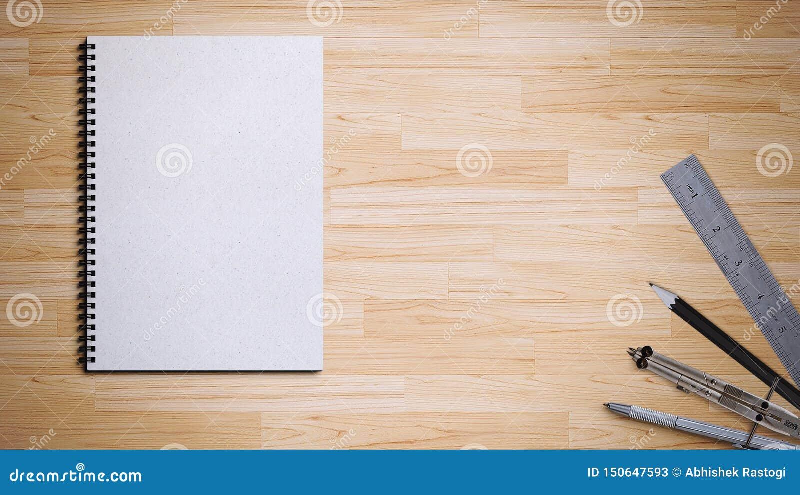 Libro espiral con la pluma, el lápiz, la regla y el compás