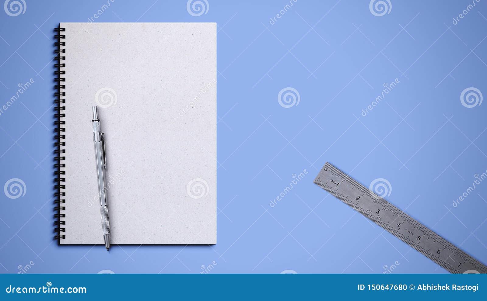 Libro a spirale con la penna e righello su fondo blu