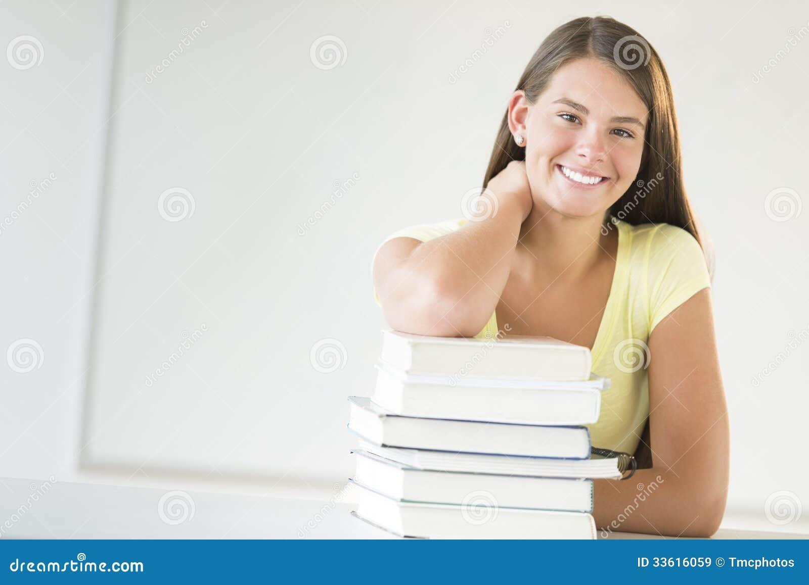Libros adolescentes de Leaning On Stacked del estudiante en sala de clase