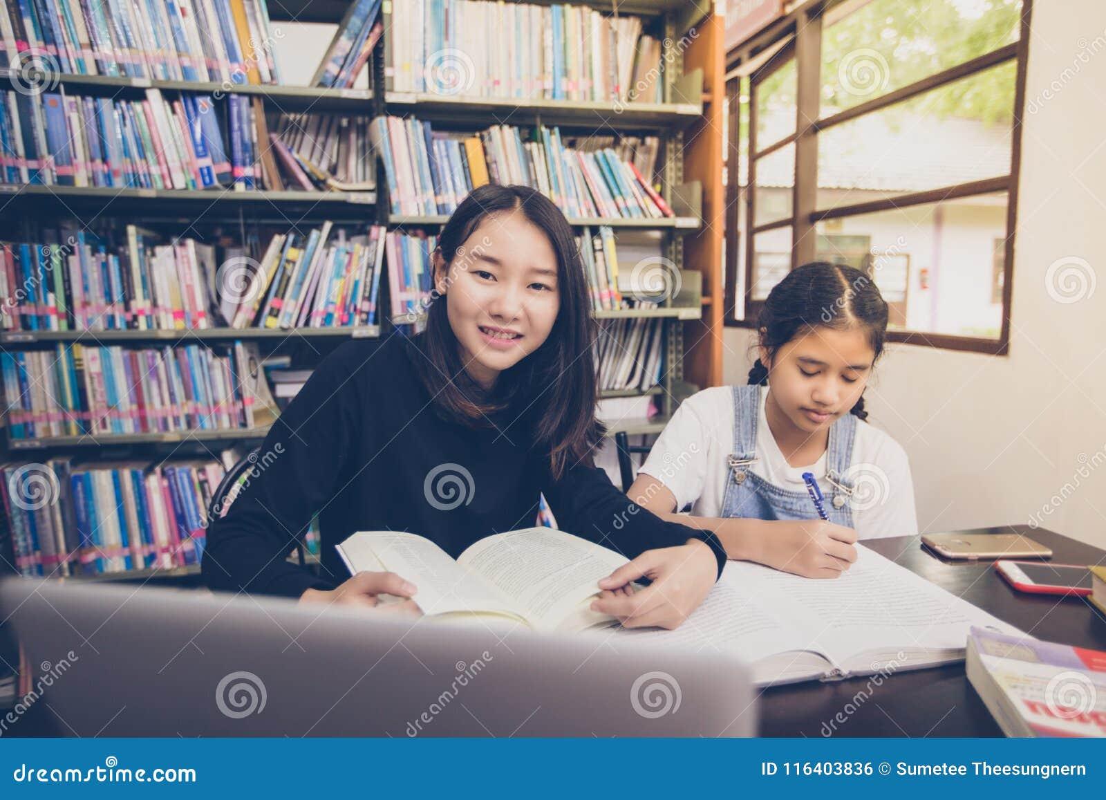 Libros de lectura asiáticos de los estudiantes en la biblioteca
