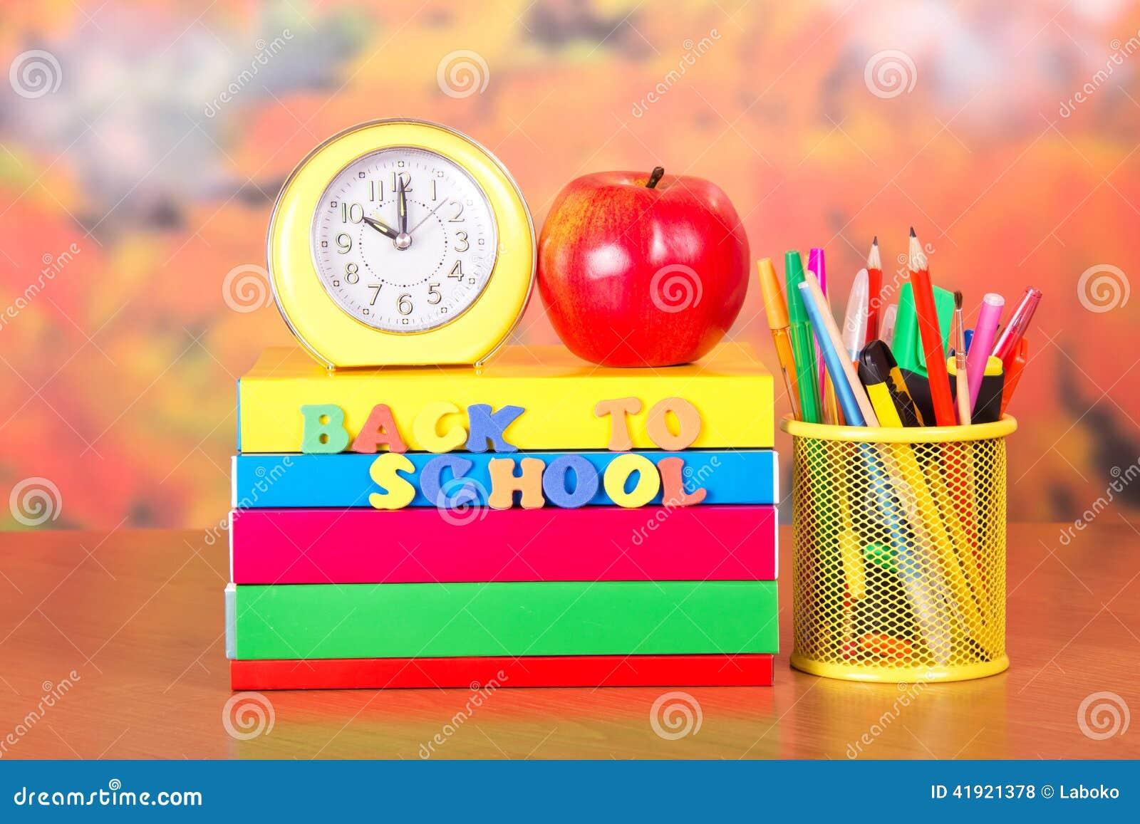 Libros, despertador, manzana roja, lápices y manijas