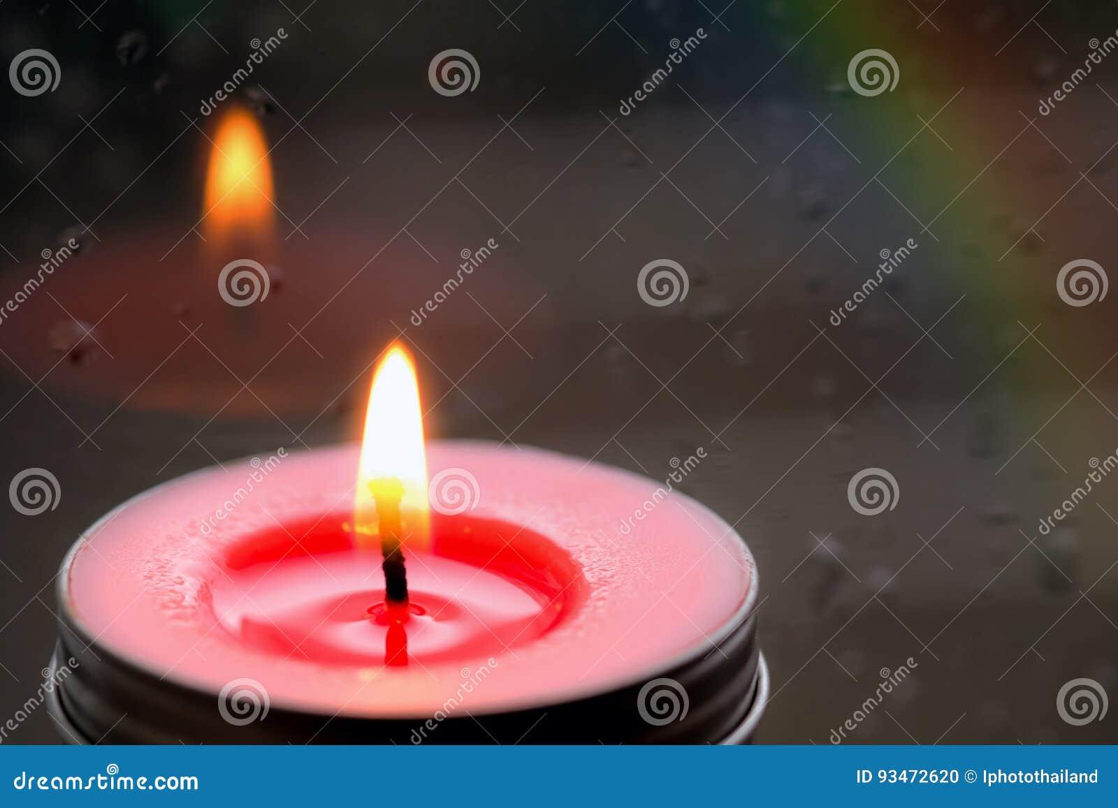 Licht Roze Kaarsen : Licht van roze kaars in de voorzijde bij venster met vaag regendr