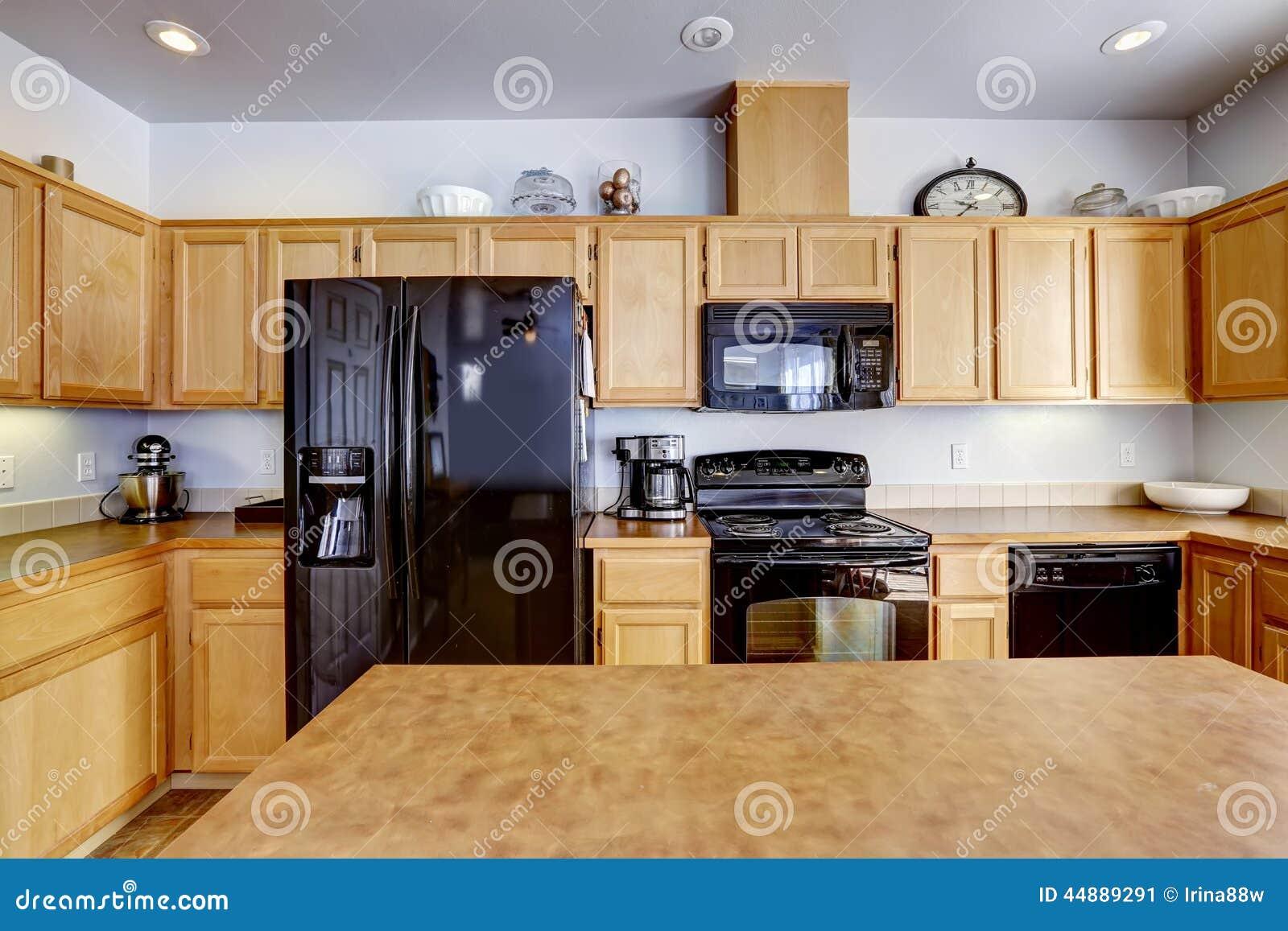Bruine keukenkasten met zwarte toestellen stock fotografie ...