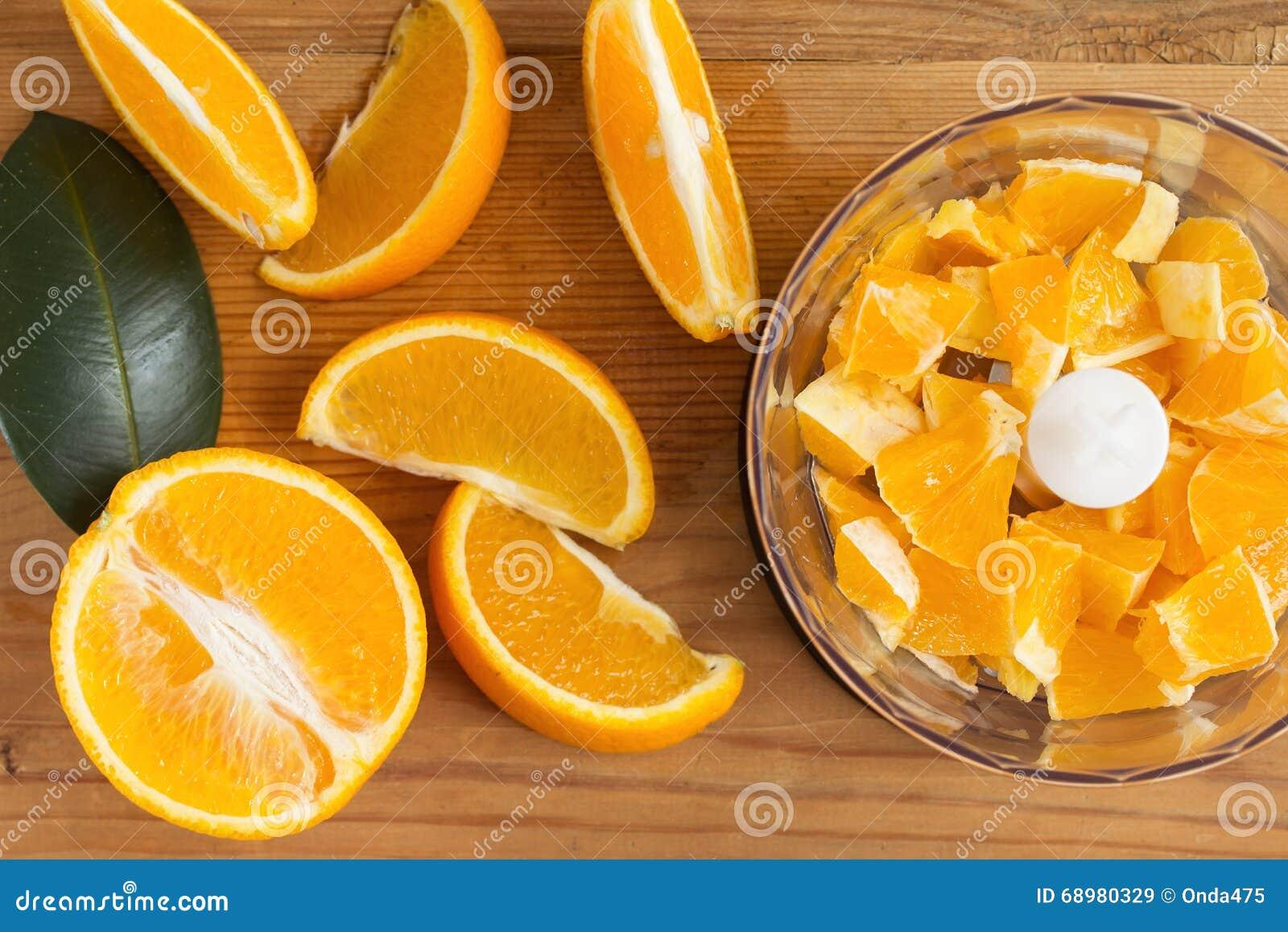 Licuadora con las naranjas jugosas en la tabla de cocina