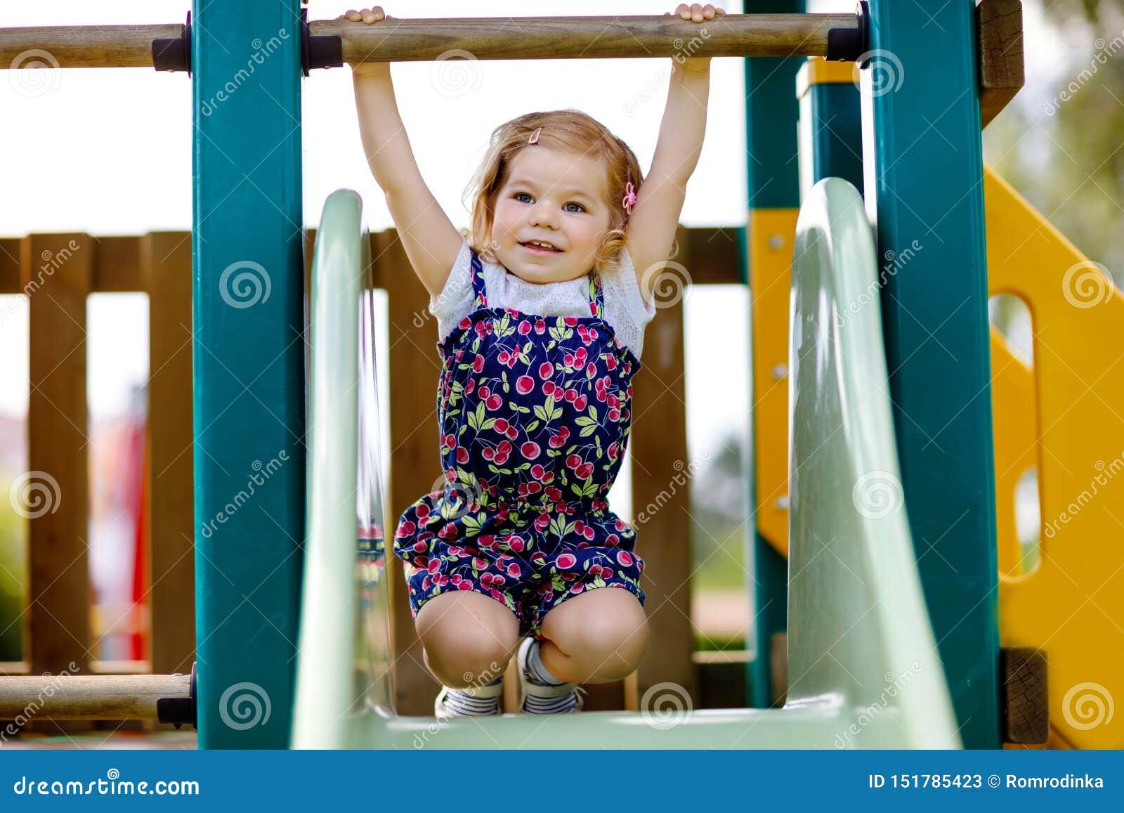 ?liczna berbe? dziewczyna bawi? si? na obruszeniu na plenerowym boisku Piękny dziecko w kolorowych skrótów spodniach ma zabawę na