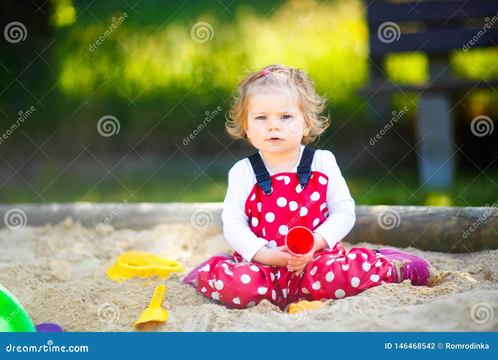 ?liczna berbe? dziewczyna bawi? si? w piasku na plenerowym boisku Pi?kny dziecko w czerwonego dzi?s?a spodniach ma zabaw? na pogo