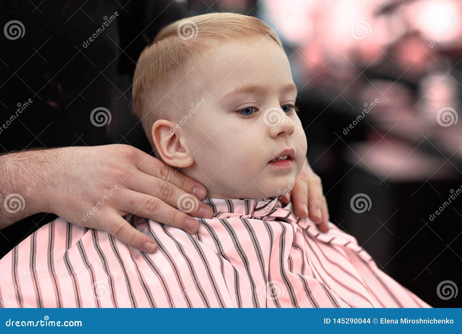 ?liczna blond u?miechni?ta ch?opiec z niebieskimi oczami w fryzjera m?skiego sklepie ma ostrzy?enie fryzjerem R?ki stylist