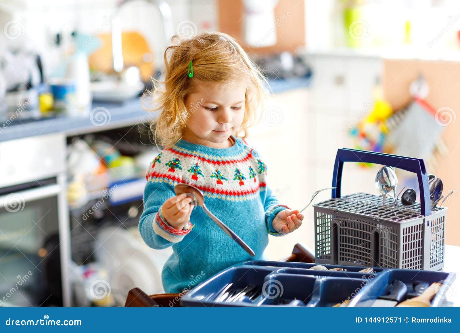 ?liczna ma?a berbe? dziewczyna pomaga w kuchni z naczynie pralk? Szcz??liwy zdrowy blondynki dziecko sortuje no?e