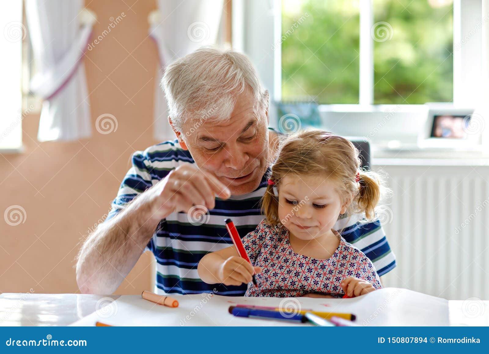 ?liczna ma?a dziecko berbecia dziewczyna i przystojny starszy dziadek obraz z kolorowymi o??wkami w domu Wnuk i m??czyzna