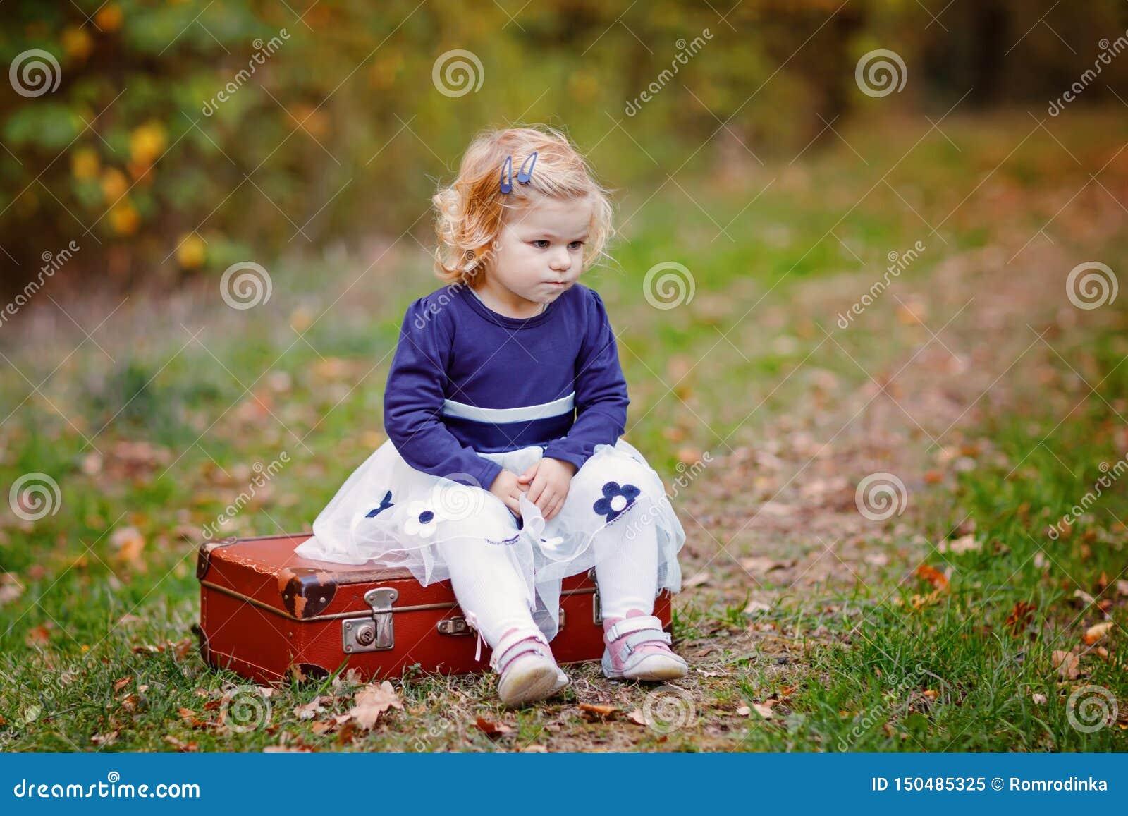 ?liczny ma?y berbe? dziewczyny obsiadanie na walizce w jesie? parku Szcz??liwy zdrowy dziecko cieszy si? chodzi? z rodzicami pogo