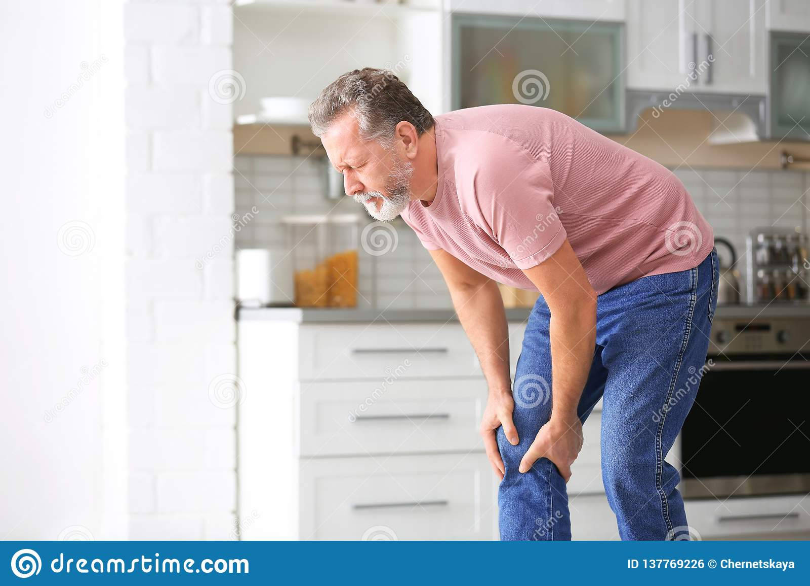 Lidande för den höga mannen från knä smärtar i kök