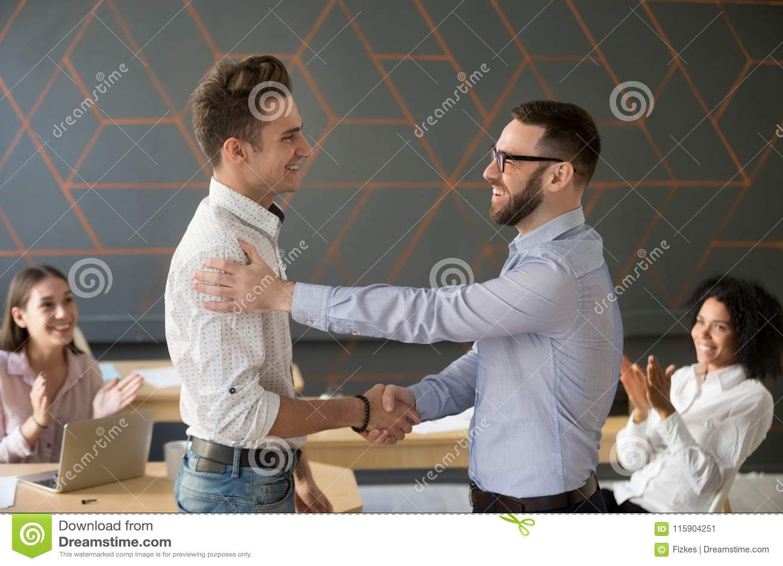 Lidera zespołu handshaking pracownika gratulowanie z professiona