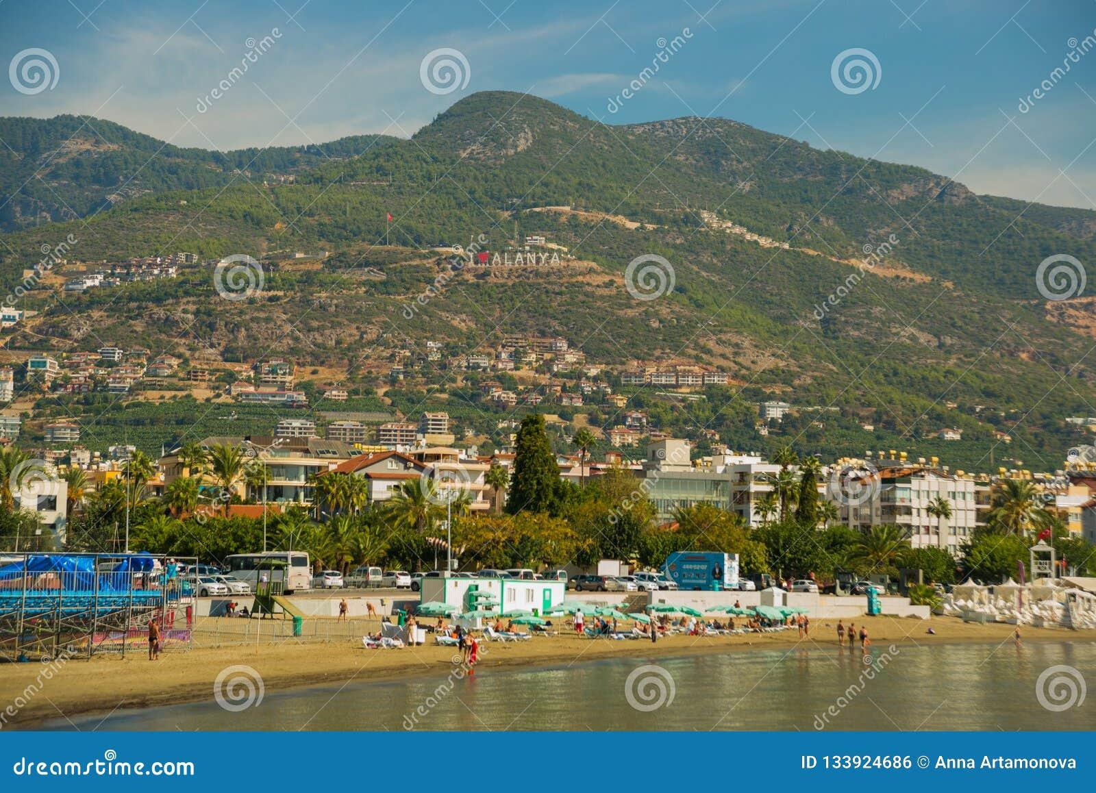 Liebe Alanya der Aufschrift I Landschaft mit Ansichten der Stadt, der Hügel und des Strandes Alanya, Antalya-Bezirk, die Türkei,