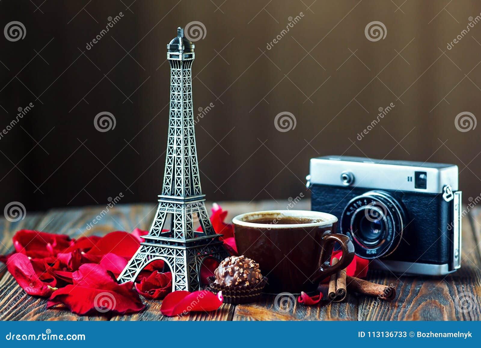 Liebe Paris! Rose, Weinlesekamera, Eiffelturm, Kaffeetasse, Schokolade und Zimtstangen auf hölzernem Hintergrund St Valentinsgruß