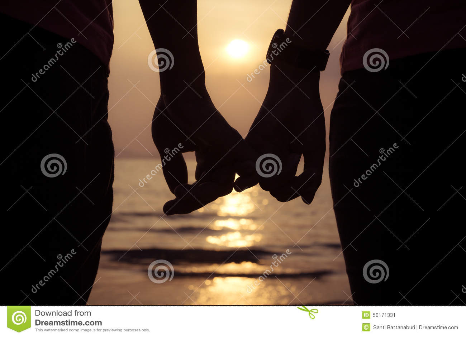 Lieben Sie Paarhändchenhaltenfinger bei Sonnenuntergang auf dem Strand