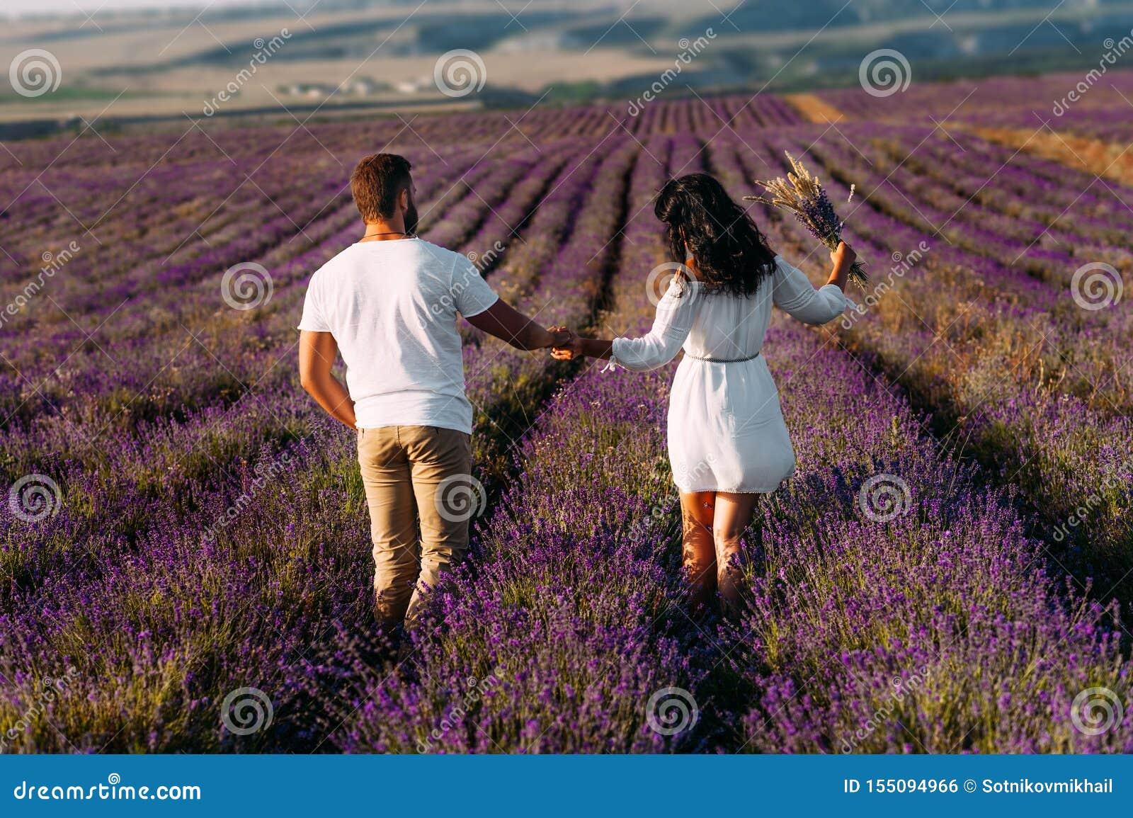 Liebendes Paarhändchenhalten auf Lavendelfeldern Glückliches Paar auf hinterer Ansicht der Blumenfelder Mann- und Frauenreisen Pa