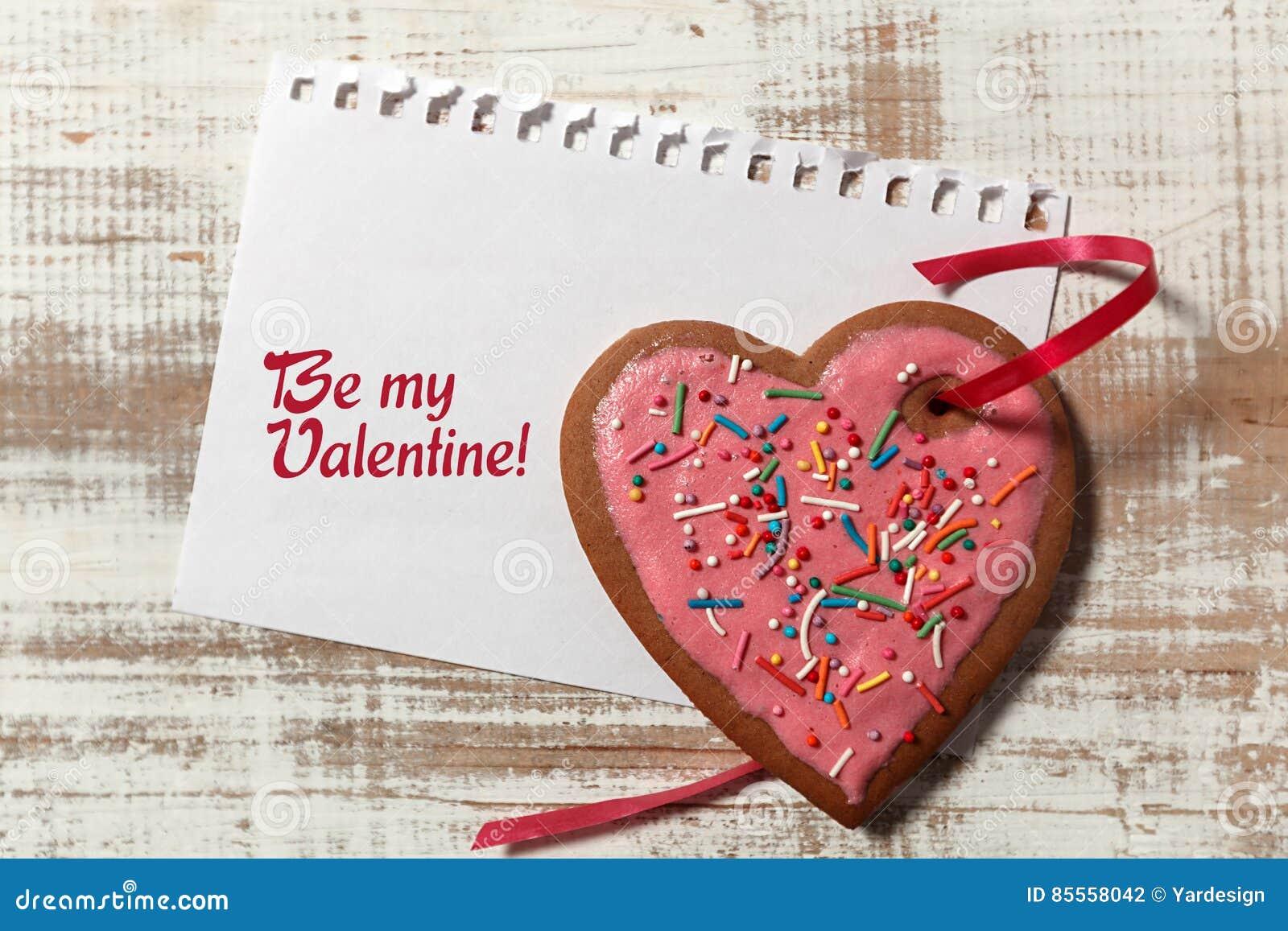 Liebesbrief auf Papier- und Plätzchenherzen mit rotem Band auf hölzernem rustikalem Schreibtisch