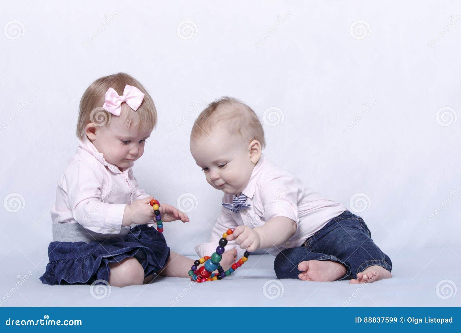 Liebesgeschichte von zwei netten Kindern Säuglingsbaby und Junge, die mit bunten Perlen spielt