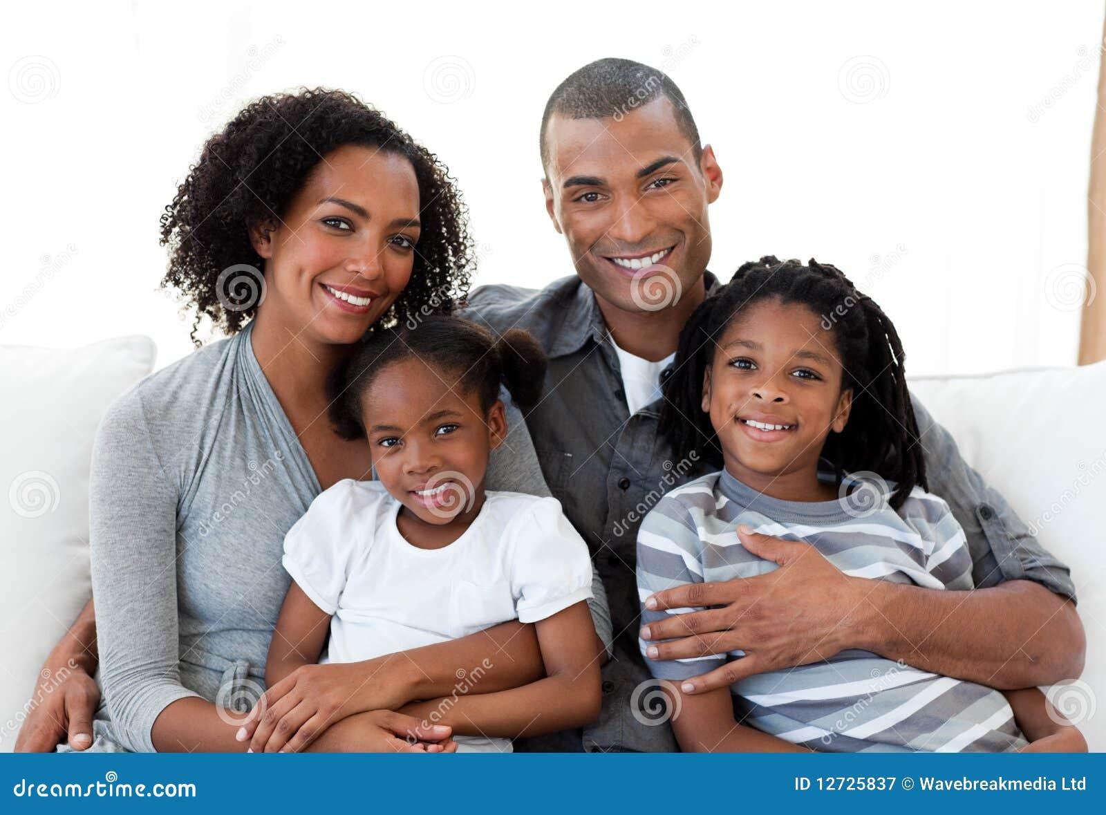 Liebevolle Familie, die zusammen auf dem Sofa sitzt