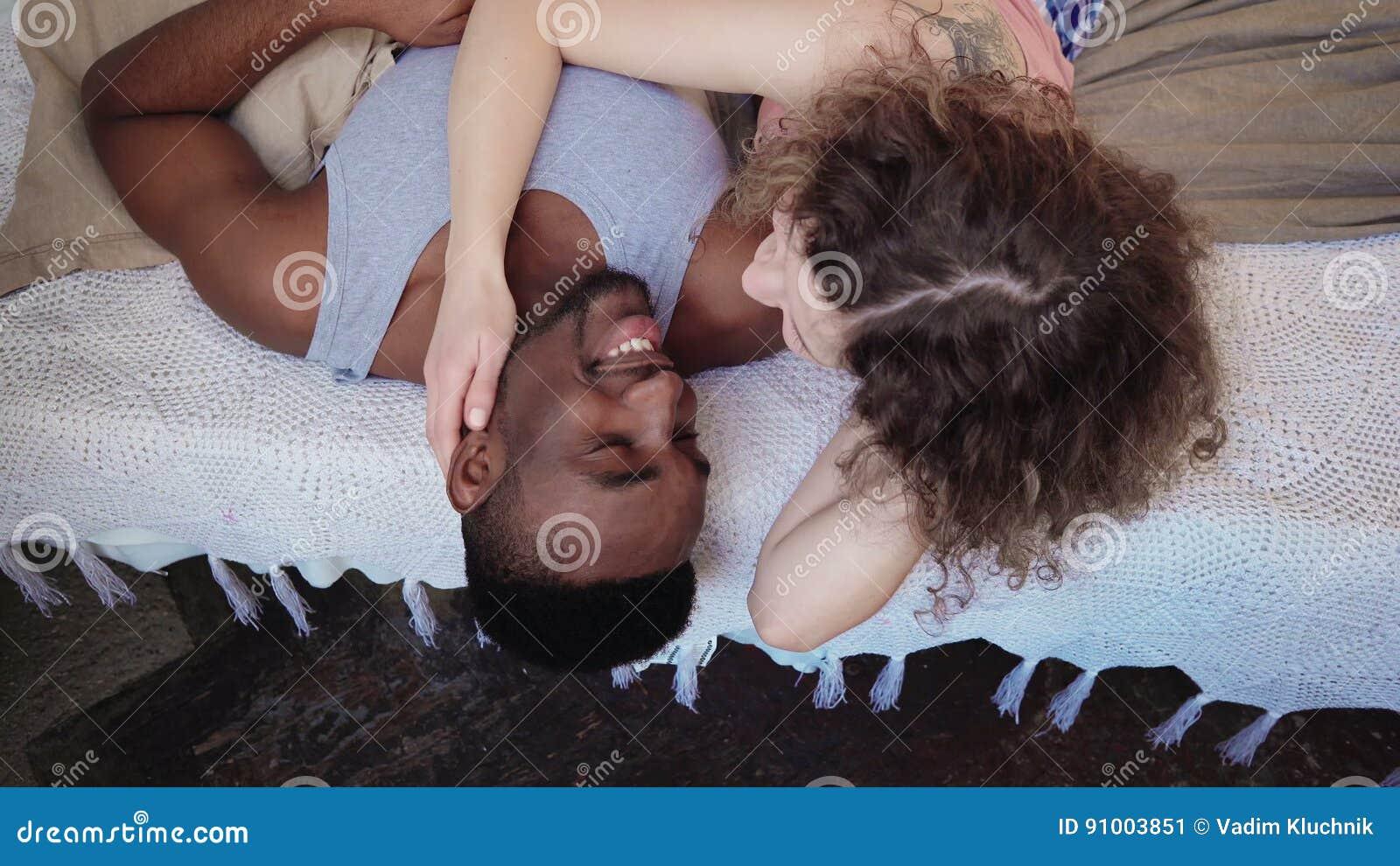 Liebevolle gemischtrassige Paare, die auf dem Bett in den Pyjamas liegen Mann- und Frauenumarmungen, Morgen zusammen verbringend