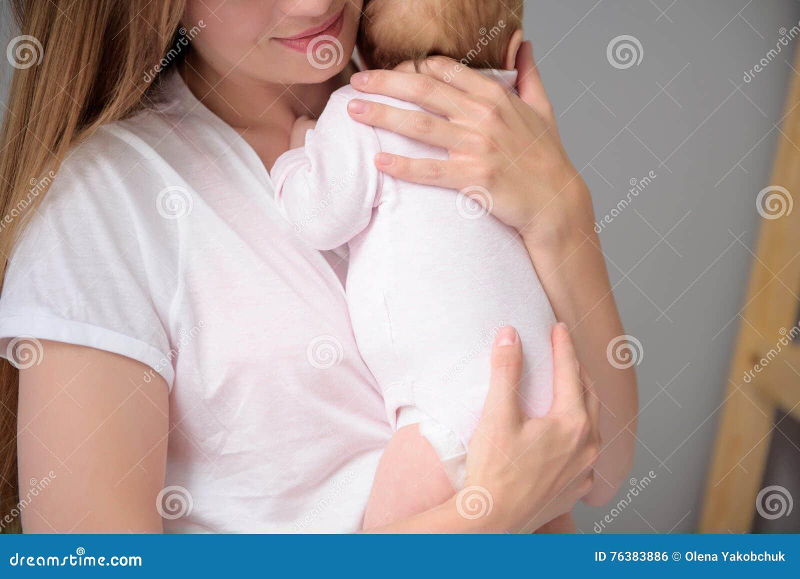Liebevolle Mutter, die für ihr Baby sich interessiert