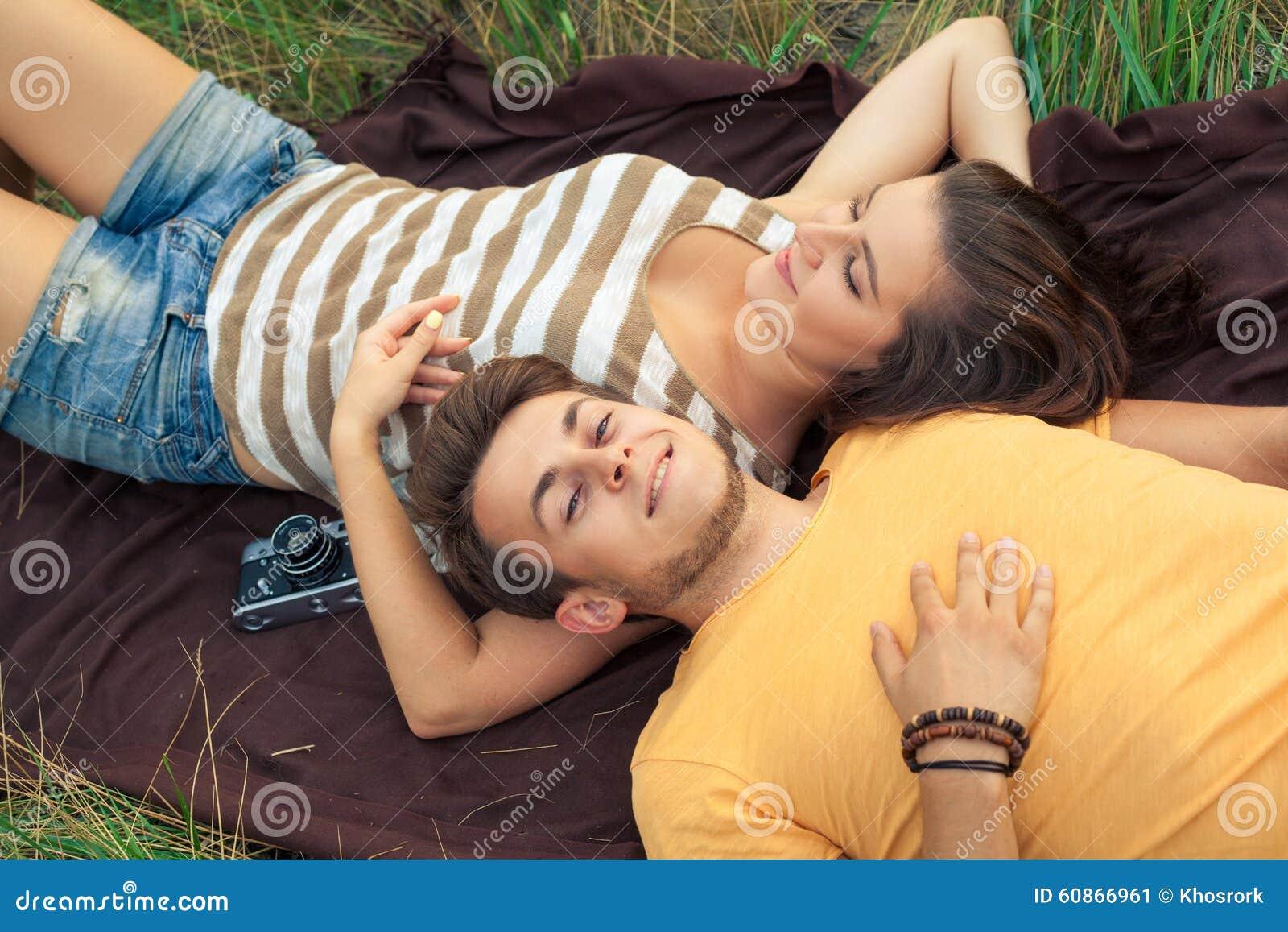 Liebevolle Paare, die sich auf Blumenfeld im herbstlichen Park, warm hinlegen