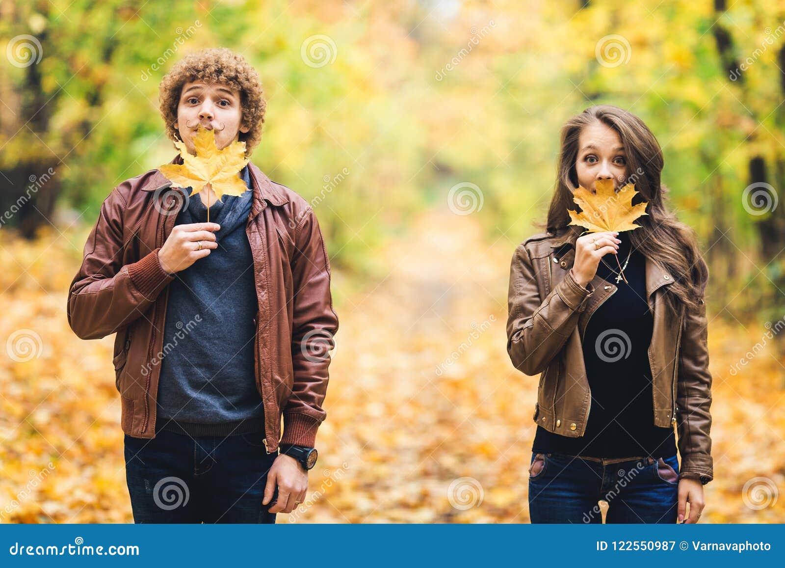Liebevolles glückliches Paar im Herbst im Park, der Herbstahornblätter in den Händen hält