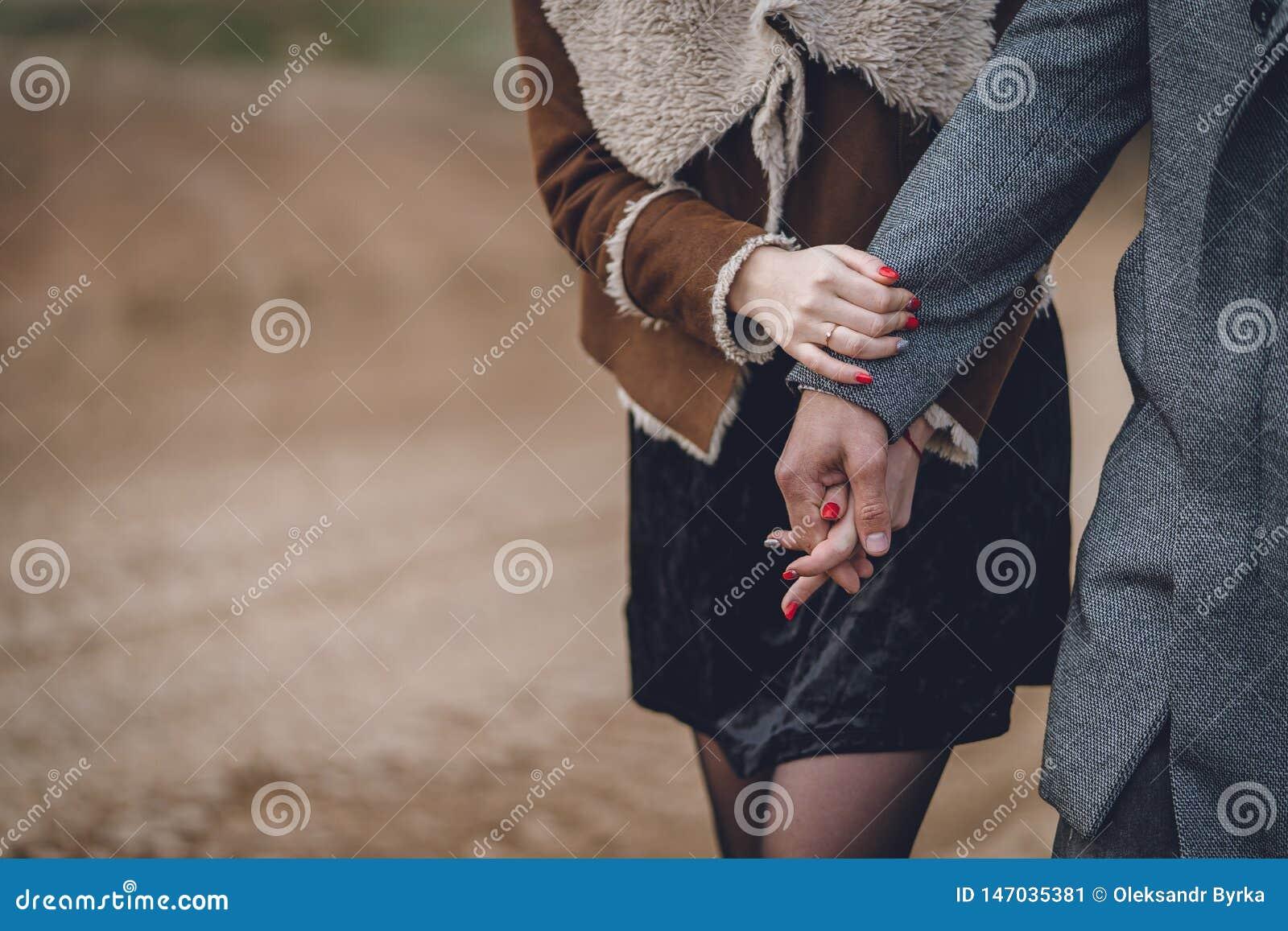 Liebhaber eines nette schöne Paares im Park oder das Feld oder die Bahn Mann im grauen Mantel und im Schal mit Mädchenfrau im bra