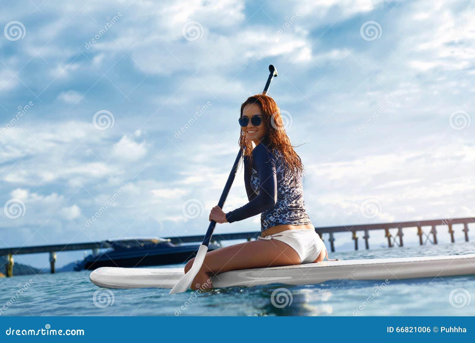 Liebhaberei Mädchen, das auf Surfbrett schaufelt Junge Frau auf dem Strand von Formentera-Insel