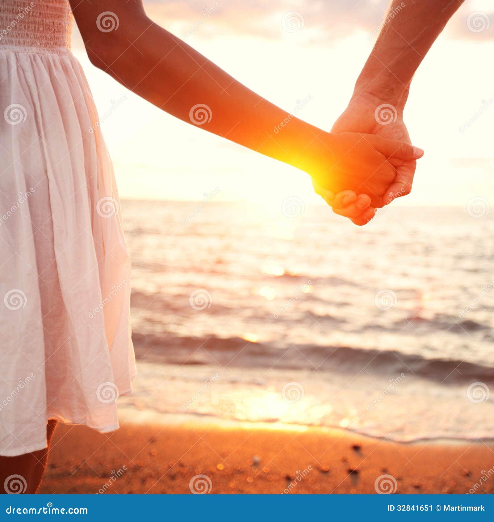 Liefde - de romantische handen van de paarholding, strandzonsondergang