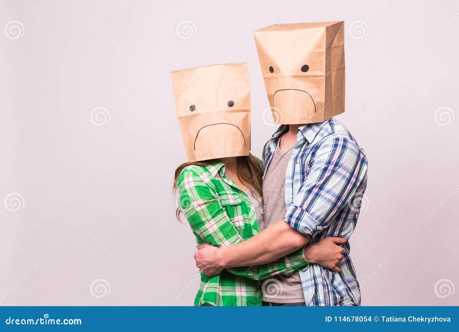 Liefde, familie en verhoudingsproblemenconcept - ongelukkig paar die hun droevige gezichten behandelen met document zak over wit