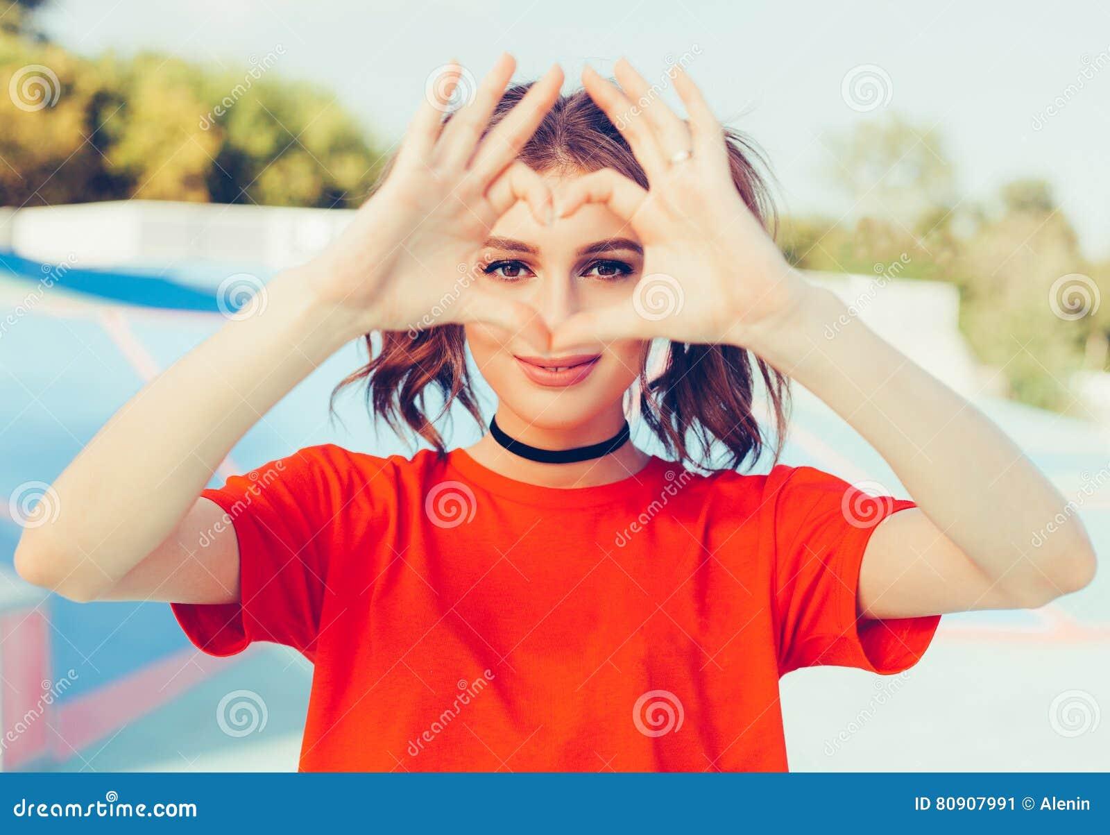 Liefde Portret die gelukkige jonge roodharigevrouw glimlachen, die hart maken ondertekenen, symbool met handen Het positieve mens
