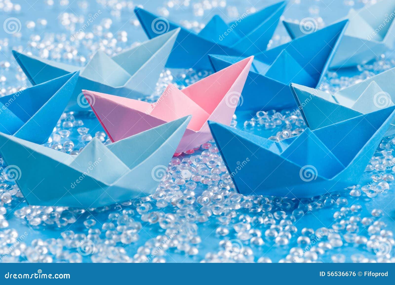 Liefdeboot: Vloot van blauwe Origamidocument schepen op blauw water zoals achtergrond die roze omringen