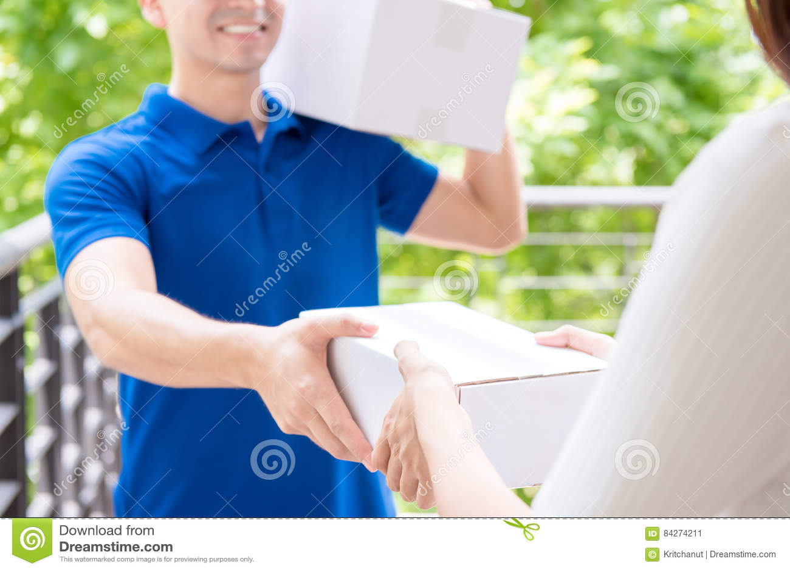 Lieferer im blauen einheitlichen liefernden Paketkasten zu einer Frau