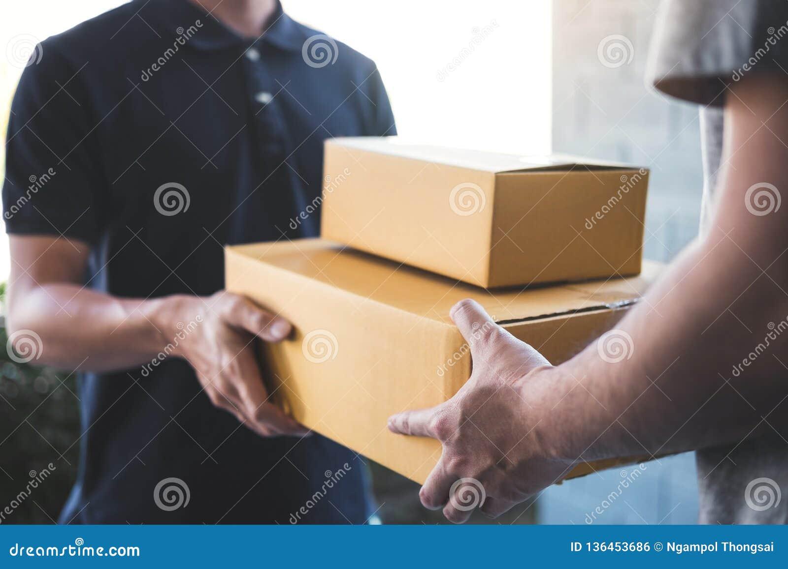 Lieferungspostmann, der der Empfänger, junges Inhaberannehmen Paketkasten des Pappschachtelpakets vom Postenversand, Haus gibt