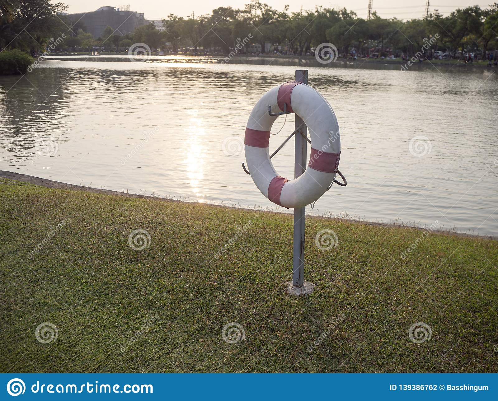 Life ring , preserver on pole in park when sunset