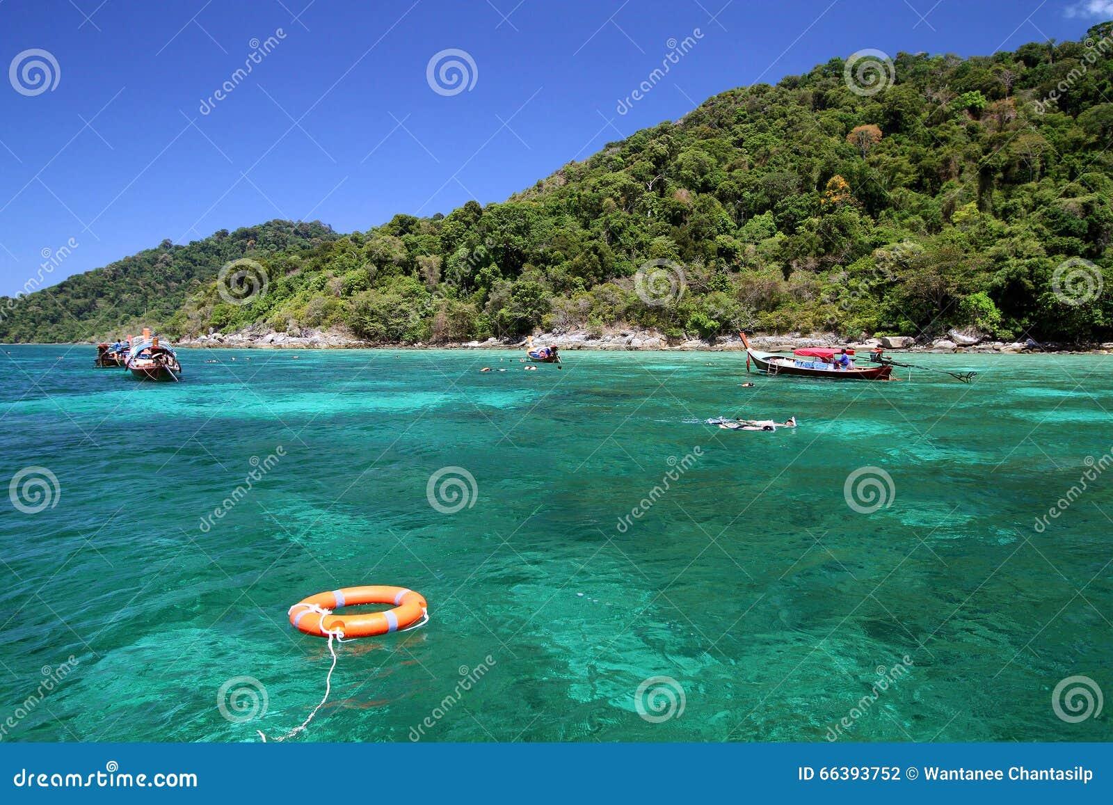 Lifebuoy podróżnicy i pierścionek cieszymy się snorkeling w jasnej wodzie