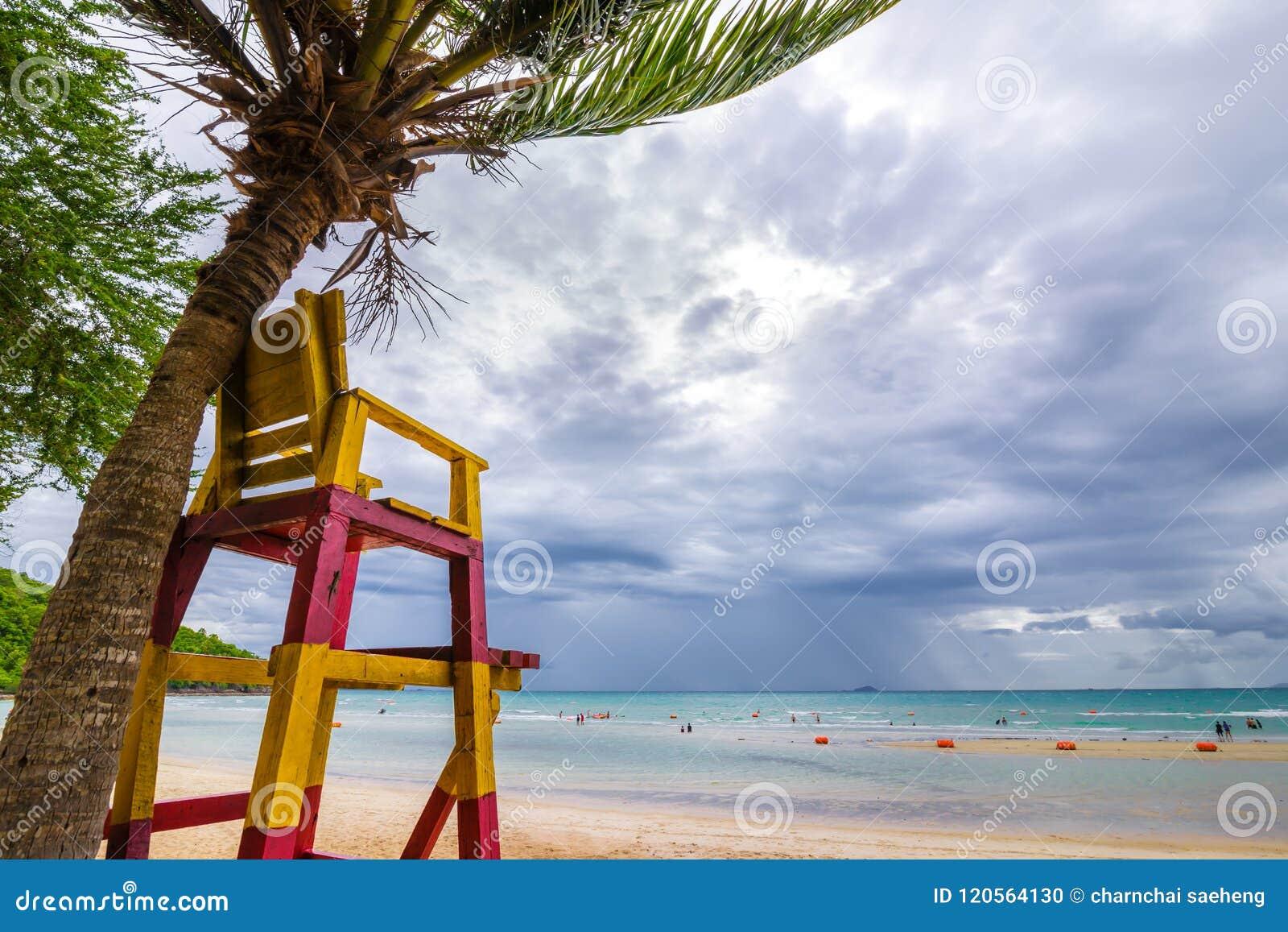 Lifeguard chair near the coconut tree on the beach with a rain cloud.