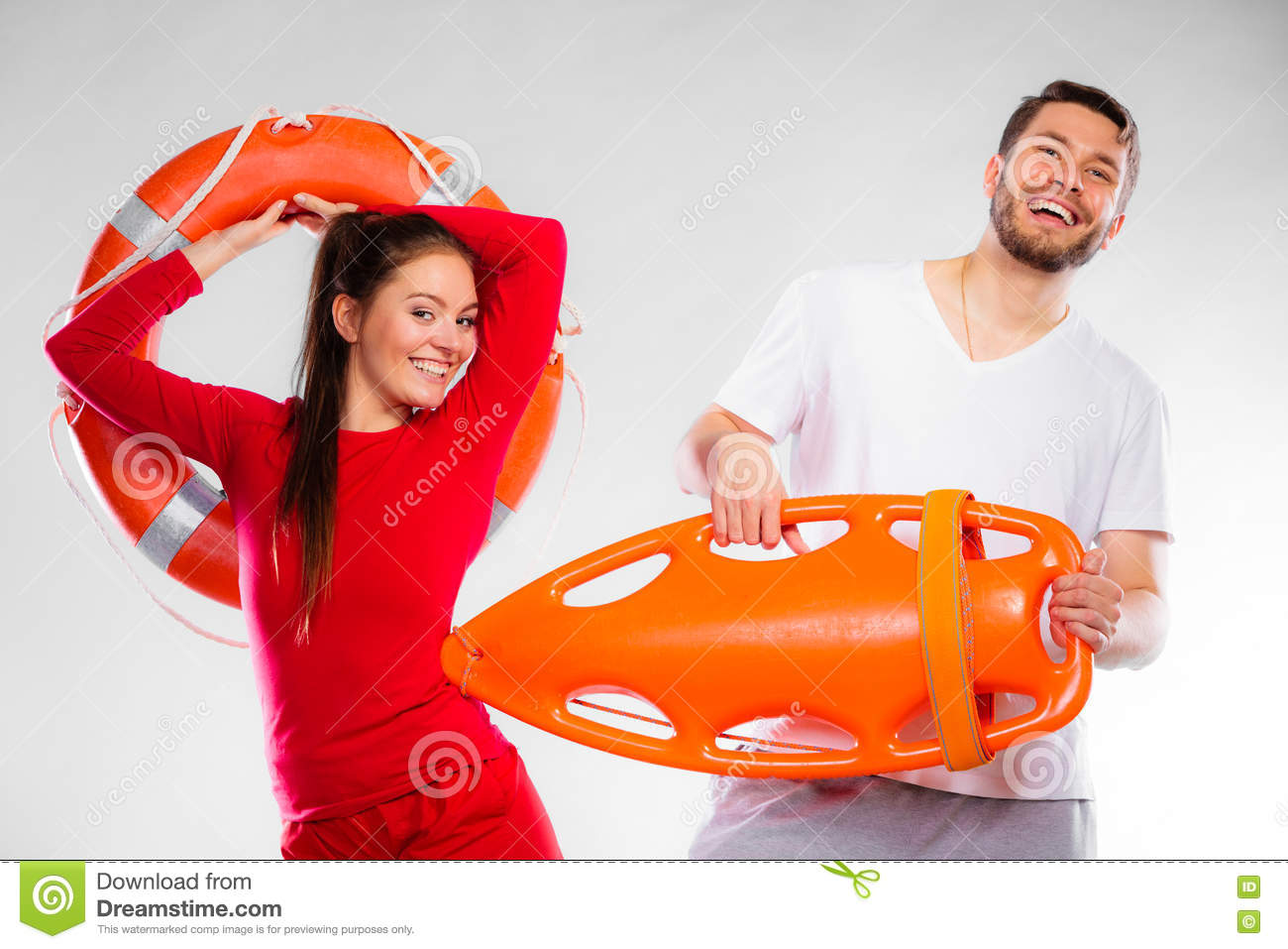 a05c91a66bb Accident prevention and water rescue. Young men and women lifeguard couple  on duty holding ring buoy float lifesaver equipment having fun on gray