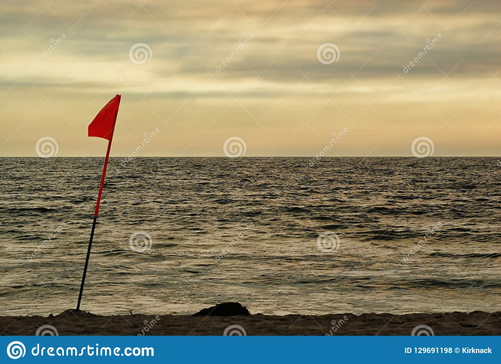 A lifeguard`s flag in the afternoon light of an overcast beach.