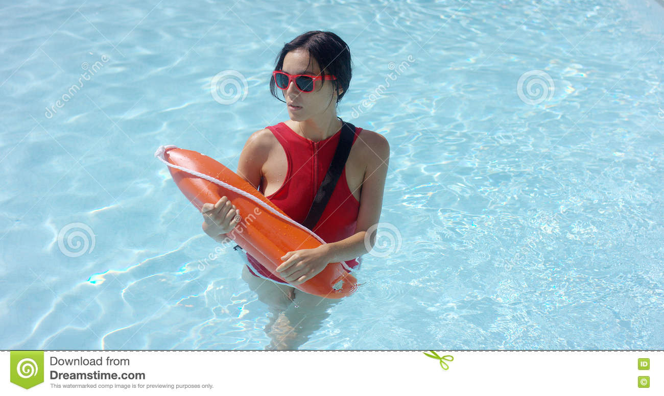 9f8c6d79e12 Single female lifeguard walking through shallow water with orange floatation  rescue device
