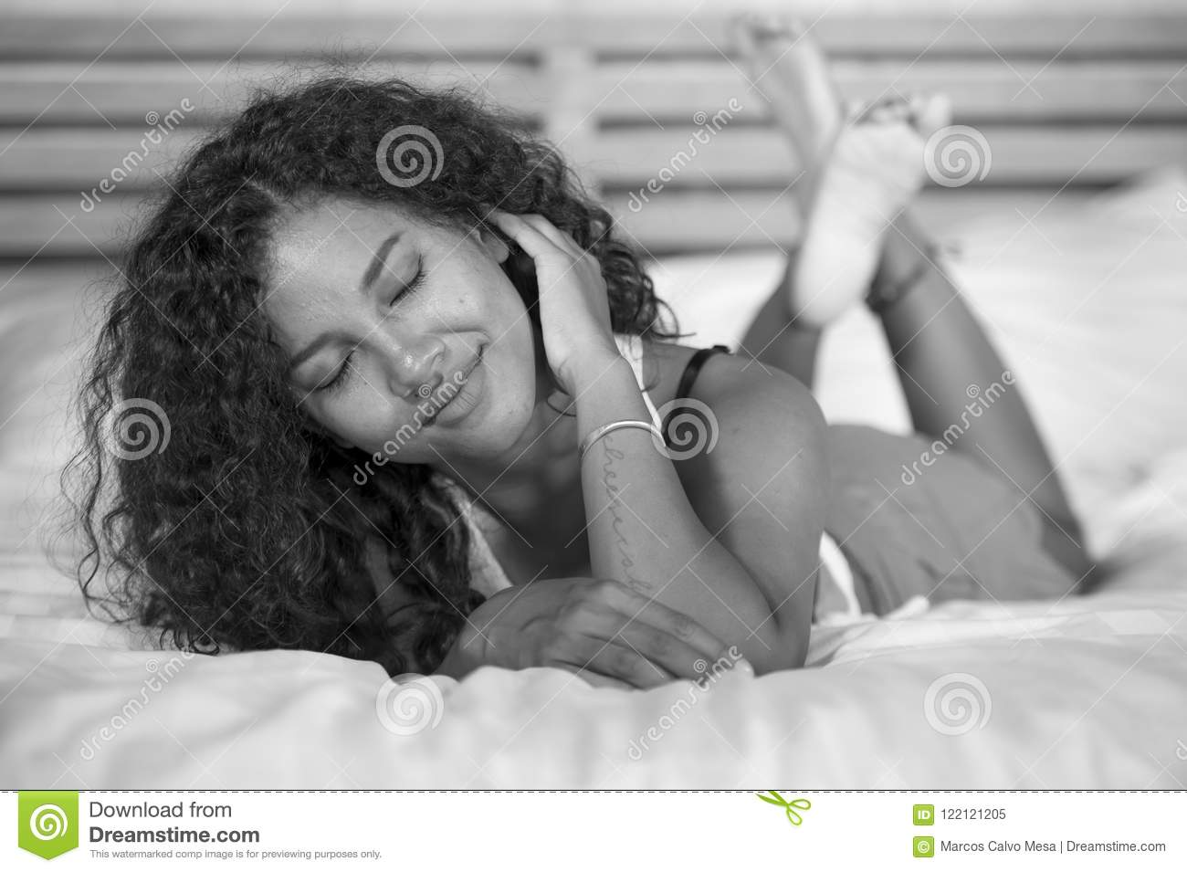 Lifestyle black and white portrait of young happy and gorgeous hispanic woman posing and playful at home bedroom lying relaxe