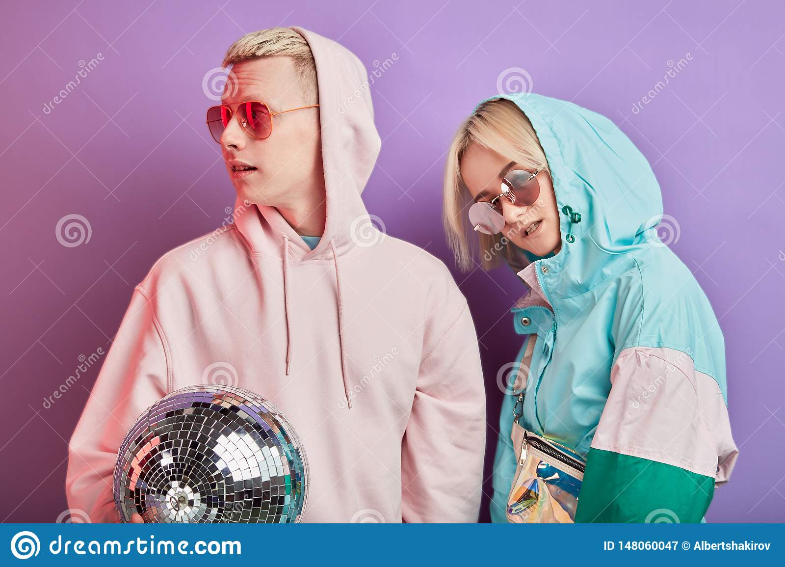 Young fashionable couple of dancers posing with disco ball on violet background