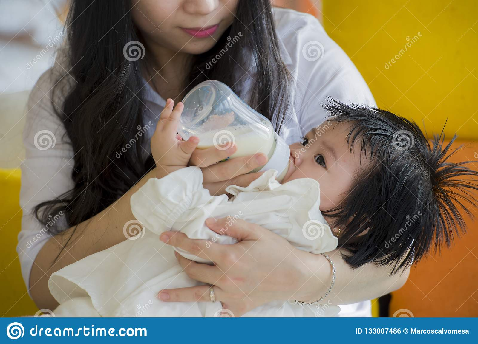 Lifestyle candid portrait of young happy and sweet Asian Japanese woman feeding her beautiful baby girl with formula bottle at