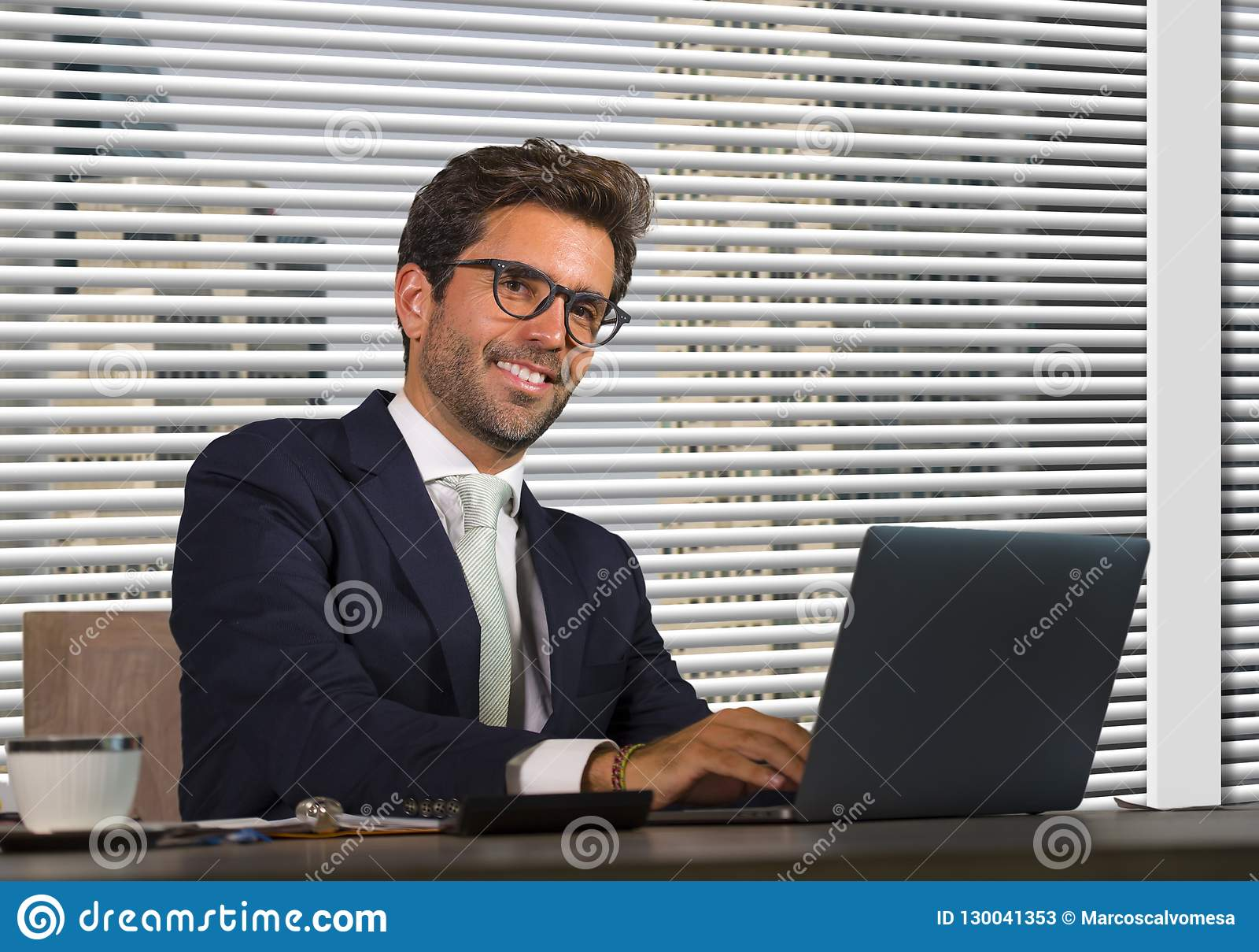 Lifestyle corporate company portrait of young happy and successful business man working relaxed at modern office sitting by window
