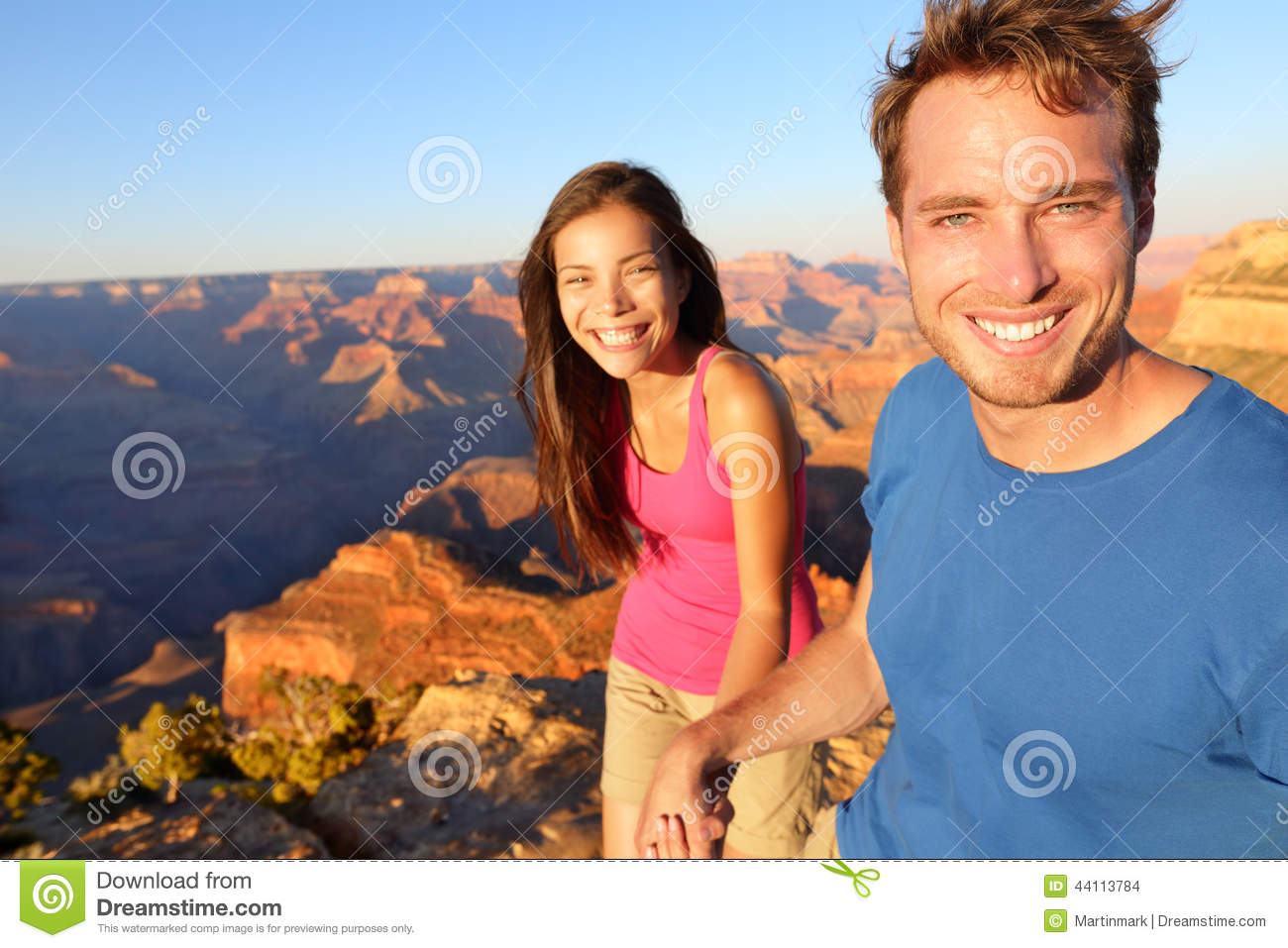 Hikers image of happy young people on hike holding hands on the South Rim  trail of Grand Canyon. Multiethnic couple, Asian woman, Caucasian man.