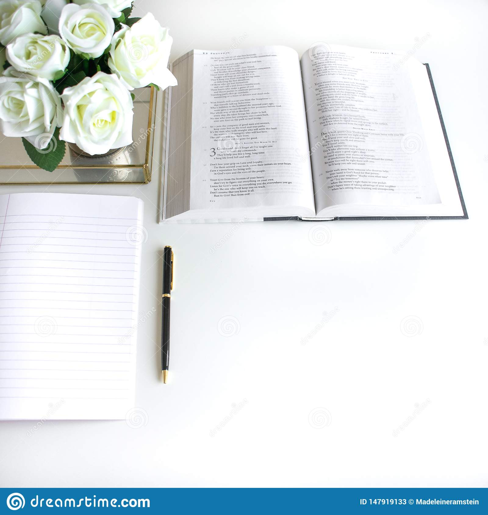 Flat lay with different accessories; flower bouquet, pink roses, open book, Bible