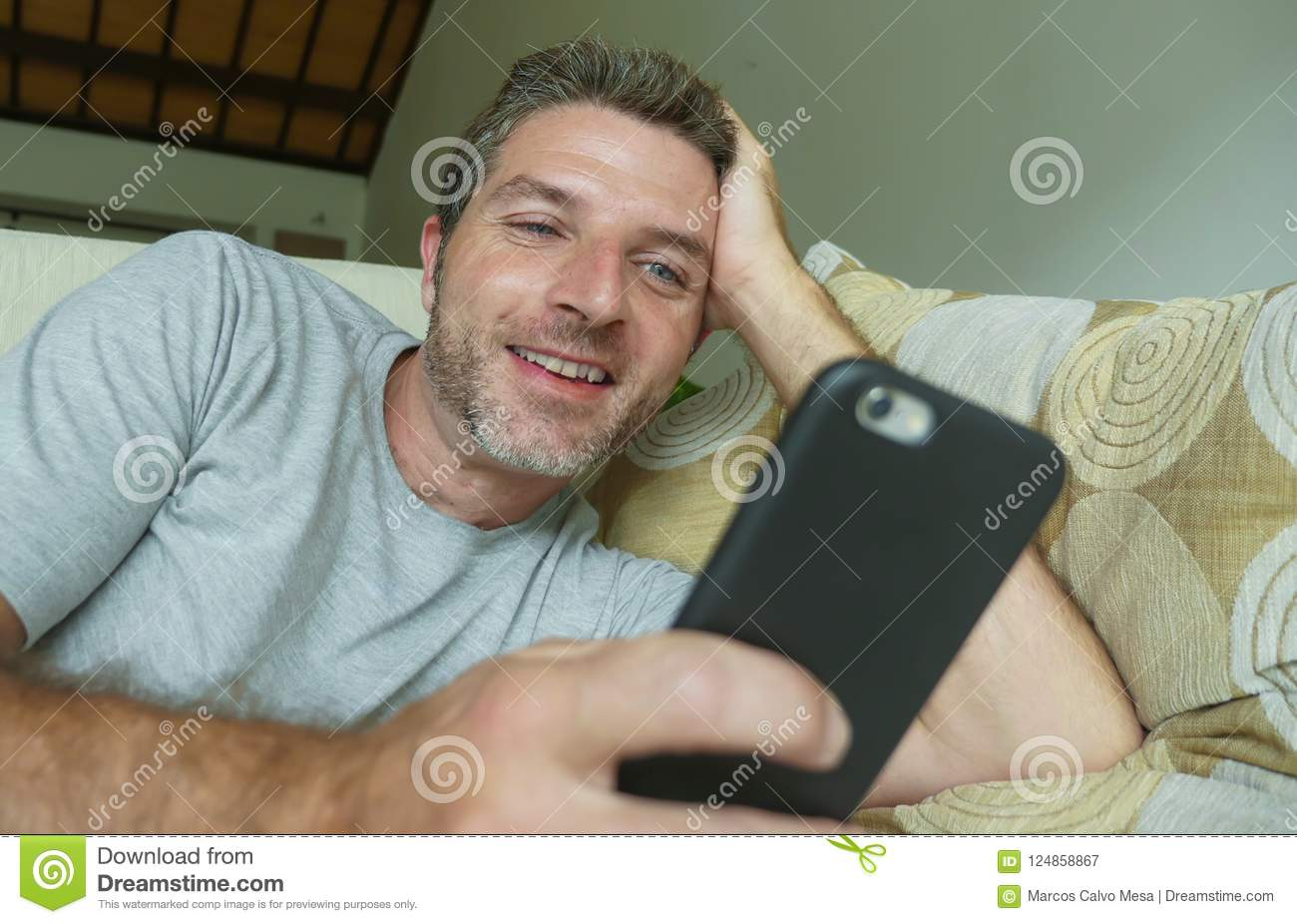 Lifestyle indoors portrait of young happy and attractive man at home sofa couch using internet social media app on mobile phone ne