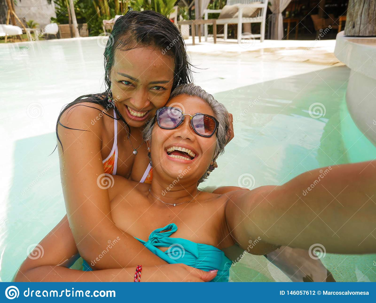 Lifestyle outdoors portrait of Asian girlfriends enjoying Summer holidays at tropical beach resort swimming pool taking selfie